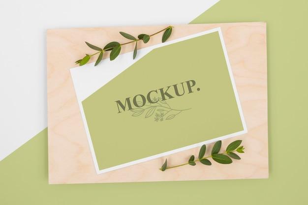 Acima, maquete de papelaria com folhas e madeira