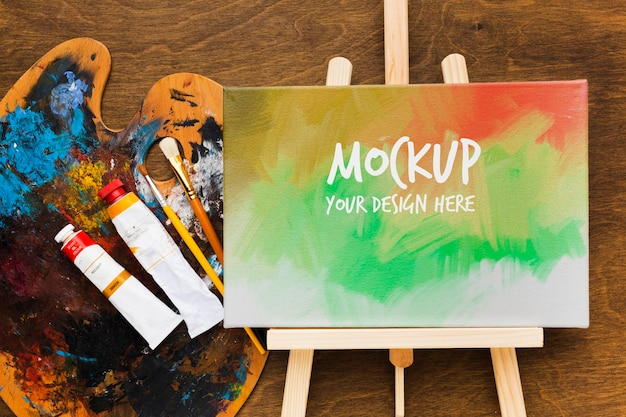 Acima, vista da mesa do artista com pintura