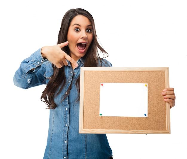 Adolescente alegre apontando para uma placa de cortiça com um papel em branco