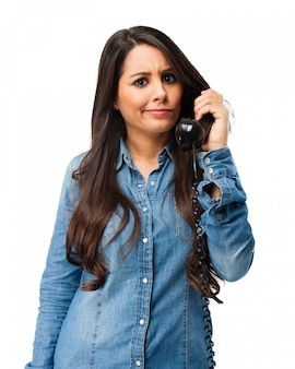 Adolescente preocupada que fala no telefone