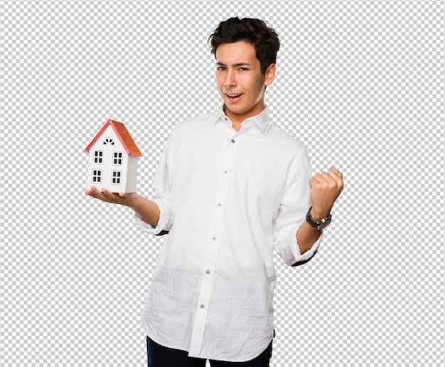 Adolescente, segurando uma casa