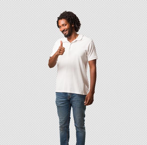 Afro-americano bonito alegre e animado, sorrindo e levantando o polegar, sucesso e aprovação, gesto ok