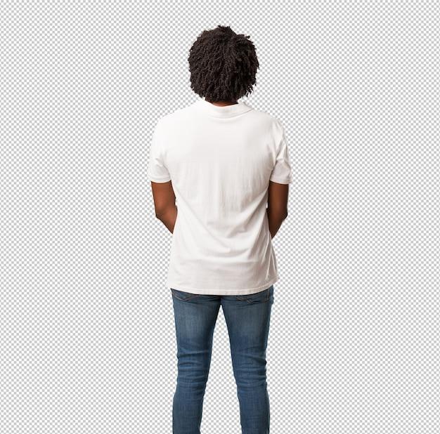 Afro-americano bonito mostrando de volta, posando e esperando, olhando para trás