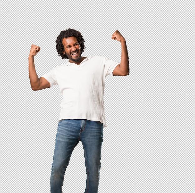Afro-americano bonito muito feliz e animado, levantando os braços, comemorando uma vitória ou sucesso, ganhando na loteria