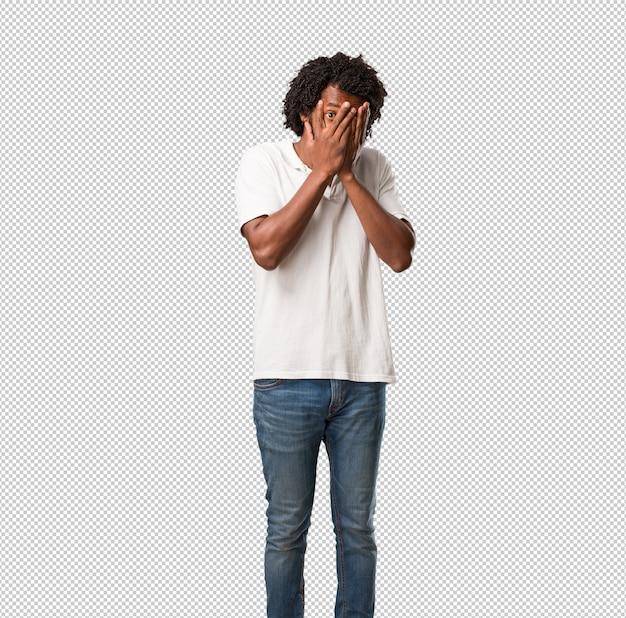 Afro-americano bonito se sente preocupado e assustado, olhando e cobrindo o rosto
