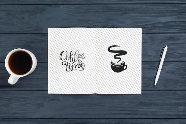 Agenda na mesa com caneta e café ao lado
