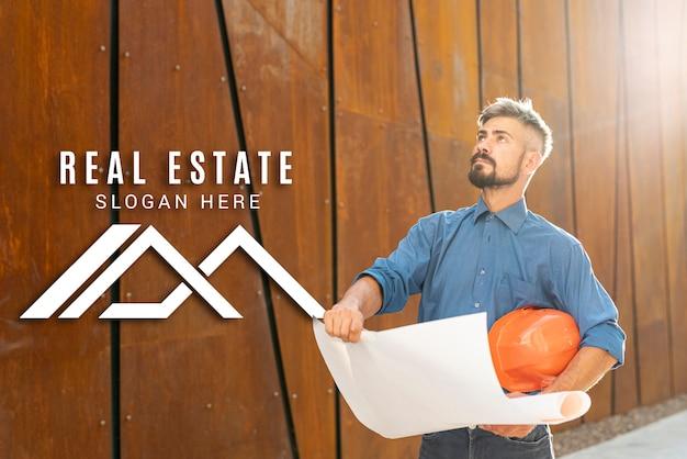 Agente imobiliário olhando para cima e segurando planos