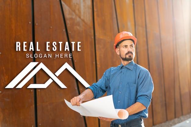 Agente imobiliário olhando para longe e segurando planos