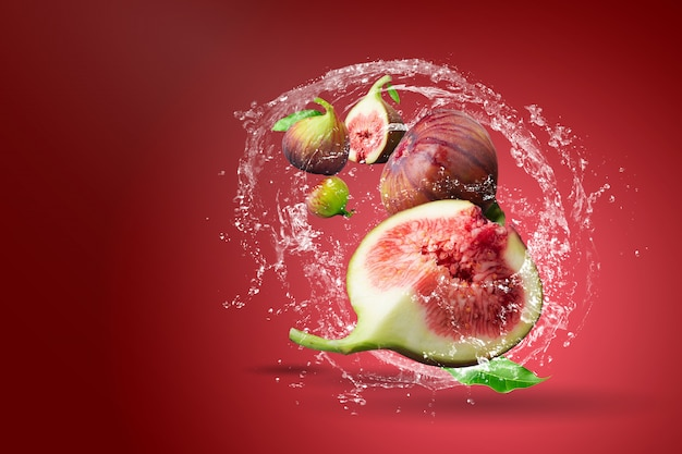 Água espirrando em figos frescos sobre vermelho