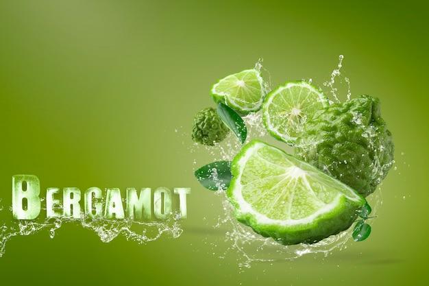 Água espirrando na bergamota fruta sobre fundo verde