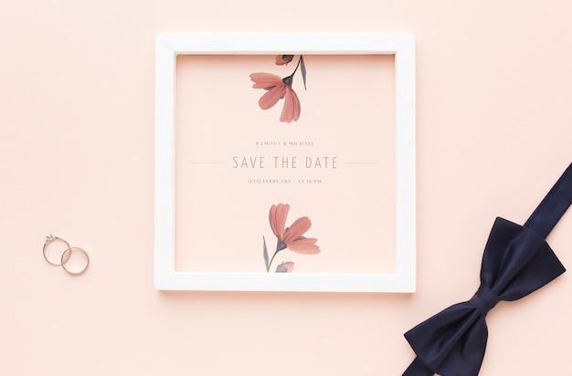 Alianças de casamento e gravata borboleta com maquete de quadro
