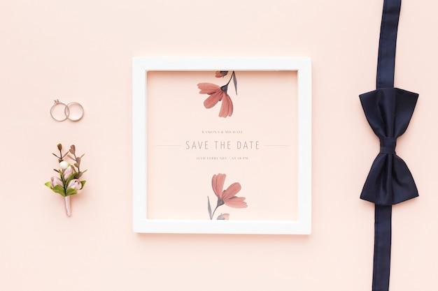 Alianças de casamento e gravata borboleta com maquete do quadro e flor