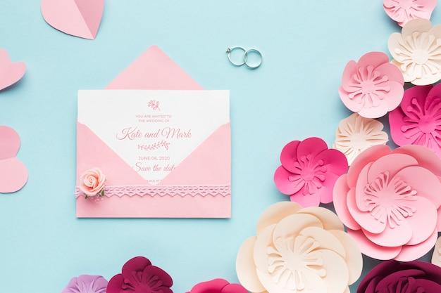 Alianças de casamento e maquete de convite com flores de papel