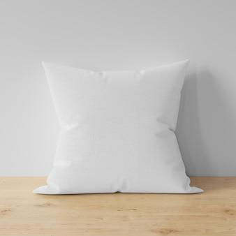 Almofada em branco na mesa de madeira
