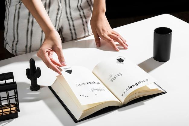 Alto ângulo de mulher usando o livro na mesa