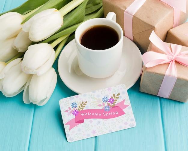 Alto ângulo de xícara de café com tulipas e presentes