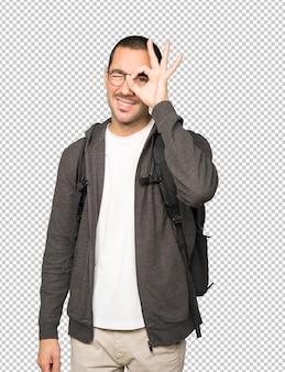 Aluno feliz usando as mãos como um binóculo