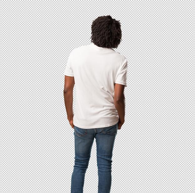 Americano africano bonito mostrando para trás, posando e esperando, olhando para trás