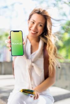 Amigável mulher apresentando smartphone maquete