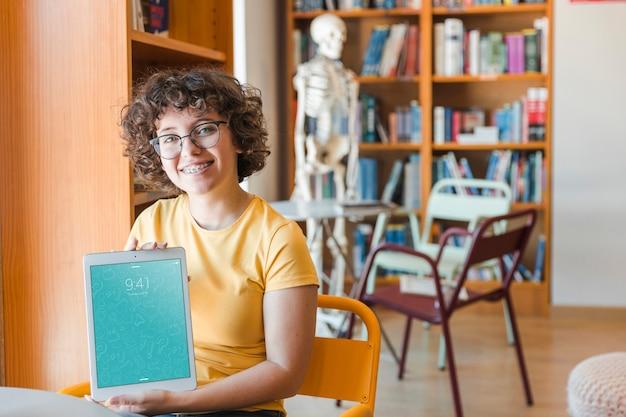 Amigável mulher segurando o tablet maquete na biblioteca