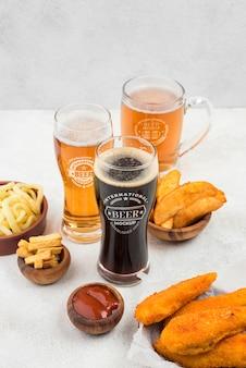 Ângulo alto de copos de cerveja com salgadinhos