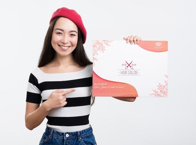 Anúncio de mock-up de salão de cabeleireiro e menina com boina francesa vermelha