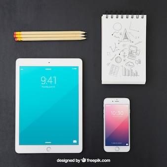Aparelhos tecnológicos, lápis e caderno com desenho