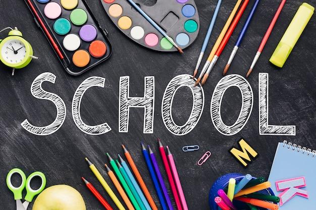 Apartamento deitar para a escola com suprimentos coloridos