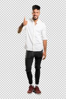 Árabe jovem com camisa branca dando um polegar para cima gesto e sorrindo