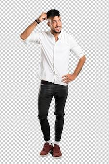 Árabe jovem com camisa branca em pé e pensando uma idéia