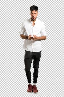 Árabe jovem com camisa branca, mantendo uma conversa com o celular com alguém