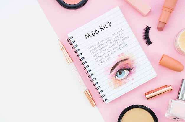Arranjo de cosméticos de maquiagem com mock-up de bloco de notas