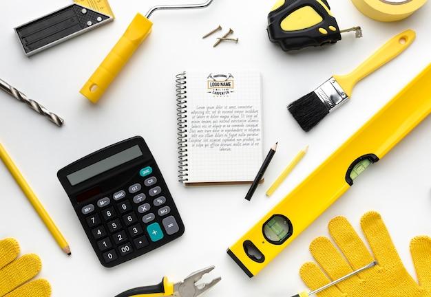 Arranjo de diferentes ferramentas de reparo com maquete do bloco de notas