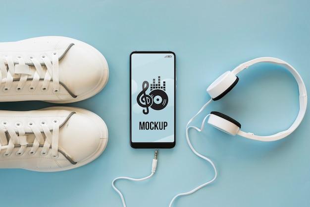 Arranjo de elementos musicais em fundo azul com maquete de telefone