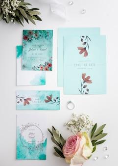 Arranjo liso leigo de elementos de casamento com maquete de convite