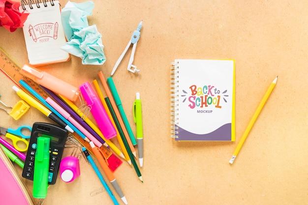 Arranjo plano de caderno e canetas