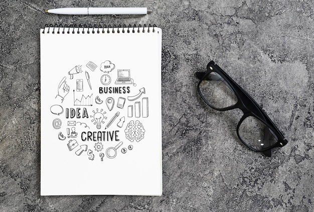 Arranjo plano leigo com caderno, óculos e caneta