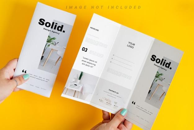 As mãos da mulher estão segurando brochura mock-up acima tabela amarela