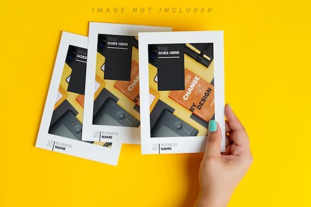 As mãos da mulher estão segurando maquete de panfleto na mesa amarela