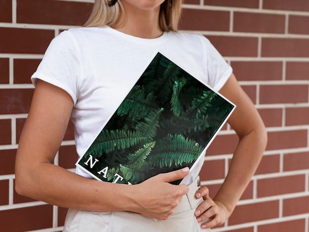 As mãos da mulher segurando uma revista de natureza simulada