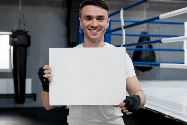 Atleta de boxe segurando uma maquete de cartão