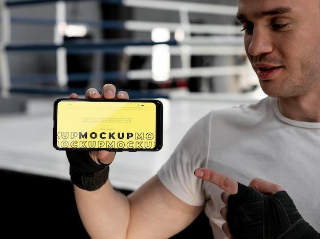 Atleta de boxe segurando uma maquete de telefone