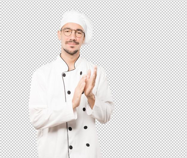 Atraente jovem chef aplaudindo o gesto