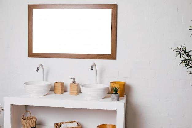 Banheiro com duas pias. espelho grande maquete pendurado na parede branca