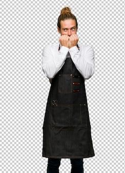 Barber homem de avental é um pouco nervoso e com medo de colocar as mãos à boca