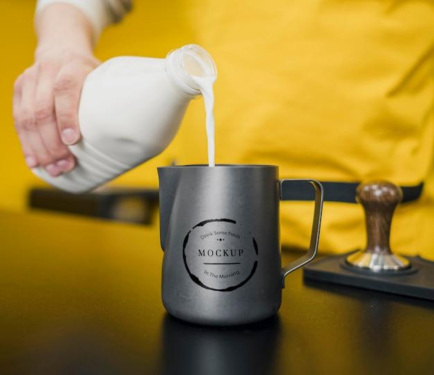 Barista servindo leite em uma maquete de jarro