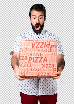 Belo homem moreno com barba segurando uma pizza
