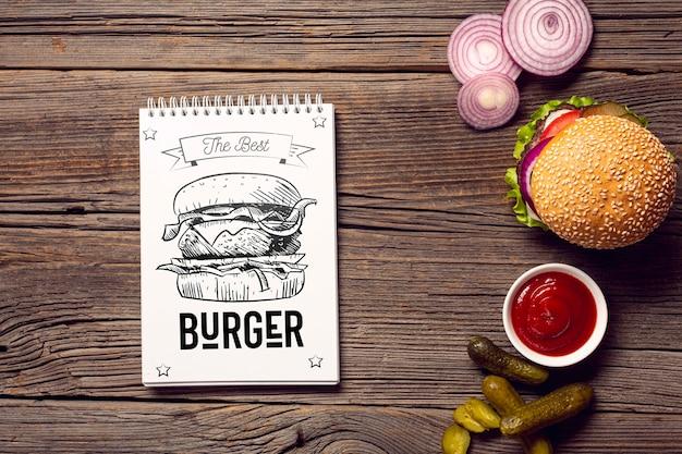 Bloco de notas com esboço de hambúrguer em fundo de madeira