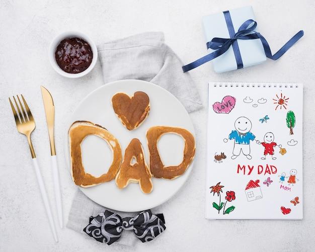 Bloco de notas com prato de panquecas e muffin para dia dos pais