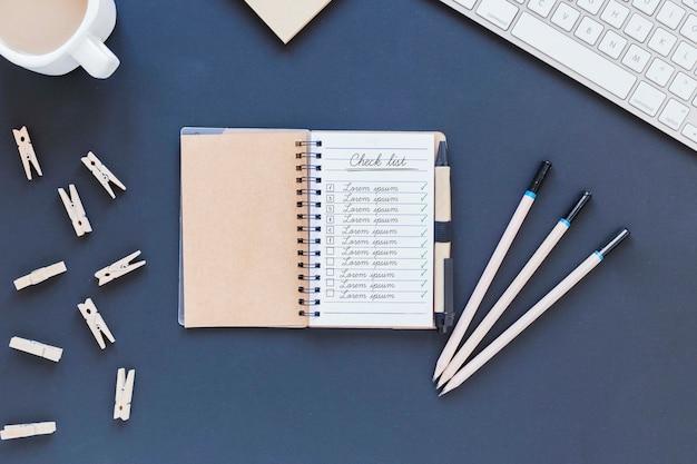 Bloco de notas da vista superior com lista na mesa